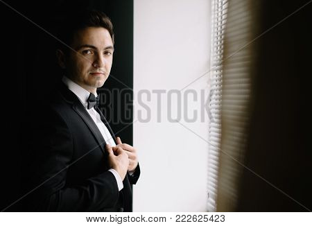 stylish groom portrait at the window while getting ready in the morning for wedding ceremony. luxury man with confident look in suit with bow tie posing in room. space for text.