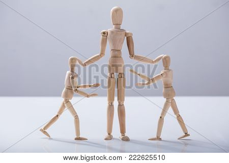 Wooden Dummy Caring For Child Dummy Against White Background