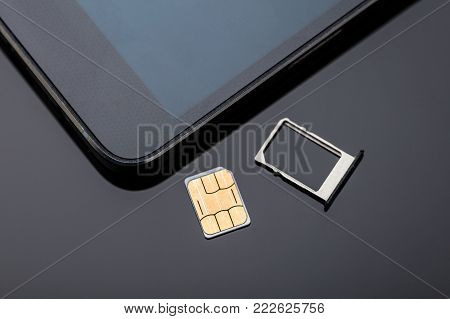 Close-up Of Nano Sim Card Ready To Insert In Smart Phone Over The Desk