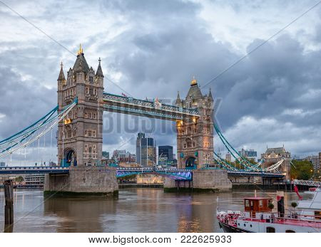 London cityscape with illuminated Tower Bridge over the River Thames at evening