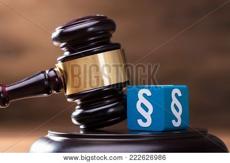 Close-up Of Blue Paragraph Block And Gavel On The Wooden Judge Soundboard