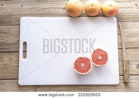 Sliced grapefruit on white cutting board with knife and three solid grapefruits sitting on wooden table