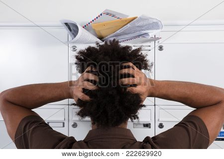 Rear View Of A Young Man Looking At Mailbox Overloaded With Junk Mails
