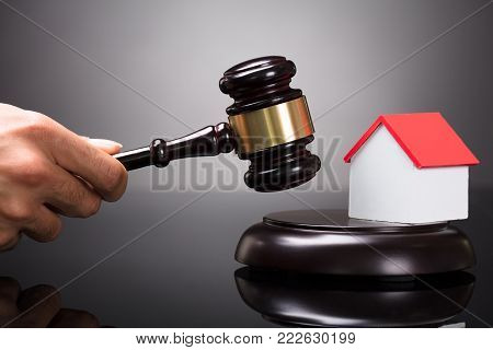 Close-up Of A Judge's Hand Striking Gavel Near House Model