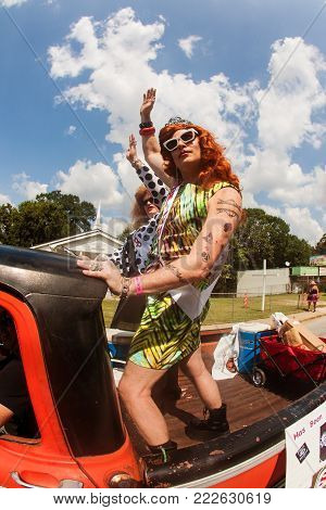 ATLANTA, GA - SEPTEMBER 2017:  Two men in drag stand in the back of a pickup truck and proudly wave to the crowd as they participate in the East Atlanta Strut in Atlanta, GA on September 23, 2017.