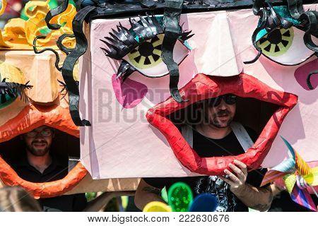 ATLANTA, GA - SEPTEMBER 2017: Men wearing huge handmade custom masks walk in the East Atlanta Strut festival parade in Atlanta, GA on September 23, 2017.