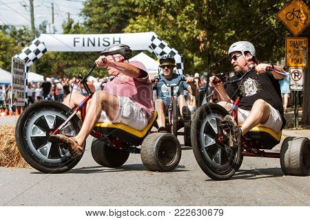 ATLANTA, GA - SEPTEMBER 2017:  Men race each other on adult big wheels in a friendly competition at the East Atlanta Strut, a fall festival in Atlanta, GA on September 23, 2017.