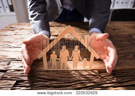 Businessperson's Hand Protecting House Model And Family Paper Cut Out On Wooden Desk