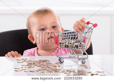 Cute Little Baby Girl Carrying Coin In Shopping Trolley On Desk