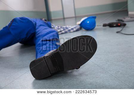 Close-up Of Handyman's Helmet With Unconscious Handyman Lying On Floor