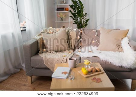 comfort, hygge, cozy home and interior concept - sofa with cushions and garland lights in living room