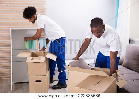Two Young Movers Placing The Books In The Shelf From The Cardboard Boxes