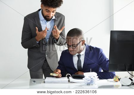 Man With Fingers Crossed Looking At Young African Auditor Analyzing Bill At Workplace