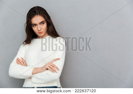 Close-up photo of upset brunette girl in soft sweater standing with crossed hands, looking aside, isolated on gray background
