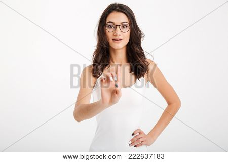 Portrait of a confident girl dressed in tank-top and eyeglasses pointing finger at camera isolated over white background