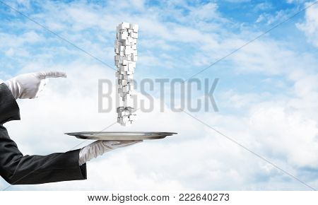 Cropped image of waitress's hand in white glove presenting multiple cubes in form of exclamation mark on metal tray and pointing on it with cloudy skyscape on background.