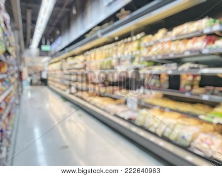 Blur grocery store background or blurry supermarket with shelves of food products and diary supplies in refrigerator shelves display