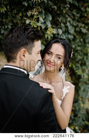 Beautiful happy young bride kissing handsome groom in sunlit park