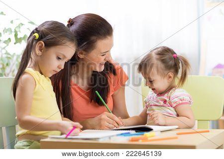 Teacher working with children kids in preschool classroom
