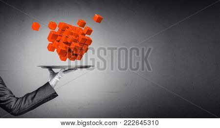 Cropped image of waiter's hand in white glove presenting multiple cubes on metal tray with gray background. 3D rendering.