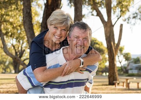 portrait of American senior beautiful and happy mature couple around 70 years old showing love and affection smiling together in the park having a romantic walk husband carrying wife on his back