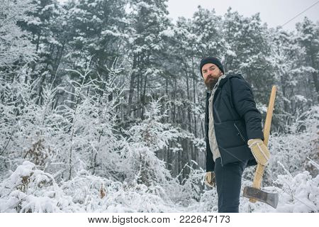skincare and beard care in winter, beard warm in winter. Man lumberjack with ax. Temperature, freezing, cold snap, snowfall. Bearded man with axe in snowy forest. Camping, traveling and winter rest.