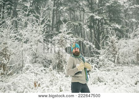 Temperature, freezing, cold snap, snowfall. skincare and beard care in winter. Bearded man with skates in snowy forest. Man in thermal jacket, beard warm in winter. Winter sport and rest, Christmas.