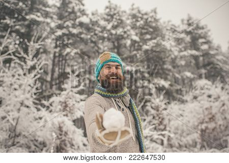 Hipster in thermal jacket, hat, scarf, beard warm in winter. Bearded man smile with snowball in snowy forest. Temperature, freezing, cold snap. Skincare, beard care in winter. Sport, rest, activity.