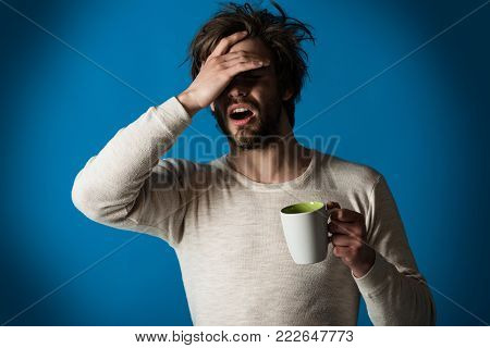 Cold and flu, single. Sleepy guy with tea cup has headache on blue background. Morning with coffee or milk. Man with disheveled hair drink mulled wine. Insomnia, refreshment and energy.