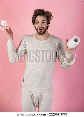 Man in underwear with disheveled hair, morning. Hygiene and sanitary. WC and restroom. Sterility and purity. Man with surprised face hold toilet paper, single. diarrhea