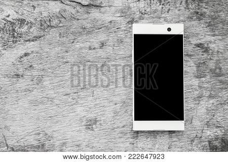 white modern mobile phone on grunge gray wood, with clipping path on moblie screen