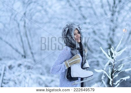 Girl happy smile with figure skates at trees in snow. Ice skating concept. Vacation, holidays, hobby, lifestyle. Woman with skating shoes in winter clothes in snowy forest. Sport, activity, health.