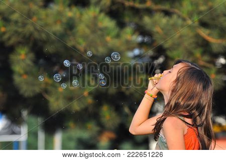 Cute girl blowing soap bubbles in summer park. Little girl play in park and blowing soap bubbles