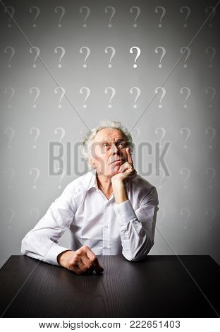 Old man is full of doubts and hesitation. Old man and question mark above his head.