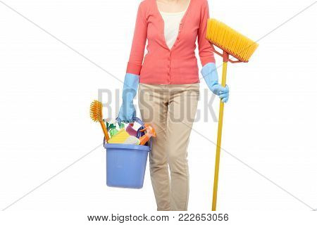 Unrecognizable housekeeper in rubber gloves holding broom and bucket with cleaning utensils in hands while standing against white background