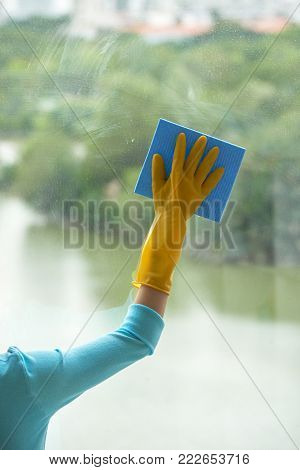 Close-up shot of unrecognizable woman wearing rubber gloves cleaning panoramic window with help of rag