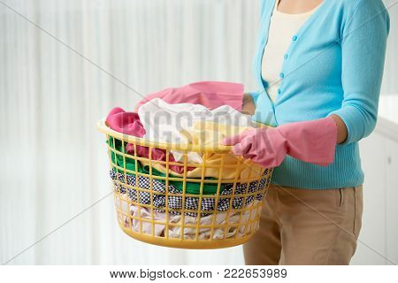 Unrecognizable woman wearing rubber gloves holding laundry basket in hands while standing against white background
