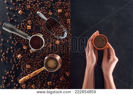 top view of person holding cup of coffee and roasted coffee beans with coffee pot, scoop and sugar