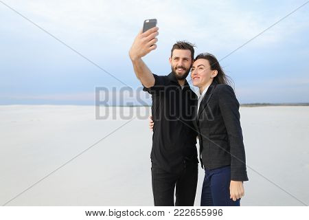 couple test camera in new smartphone, boyfriend and girlfriend taking selfies. Fellow in black shirt and girl in suit posing for photo. Concept of innovative technologies, using gadgets to make pictures or fashionable clothes.