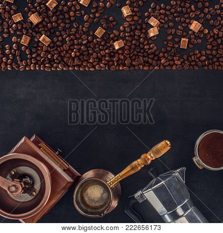 top view of roasted coffee beans, scoop, coffee grinder, coffee pot and coffee maker on black