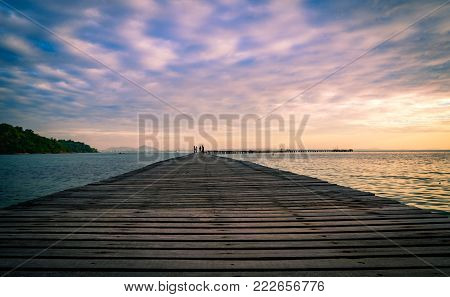Wood bridge pier with beautiful sunrise sky and clouds in the morning use for natural background. Tourist walk on wooden pier to the sea