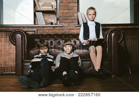 Three cute children in school clothes sitting on a sofa and reading books. School fashion. Educational concept.
