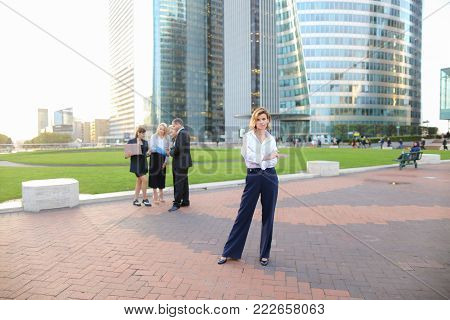 Secretary standing in La Defense Paris and looking at camera near speaking employees with boss in background. Concept of successful financial team members talking about best solutions. People dressed in business clothes making decisions with laptop outsid