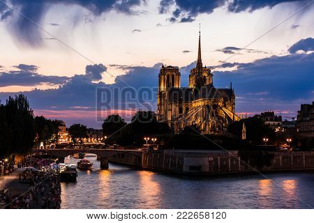 View of southern facade of Notre Dame de Paris from the Seine River at night. Notre Dame Cathedral  is a medieval catholic cathedral and finest example of french gothic architecture. Paris, France