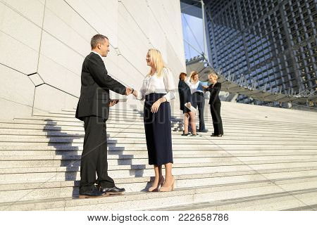 Political scientists with tablet and document cases going down stairs and talking. Concept of official journey and business trips. Young successful people discussing conference.