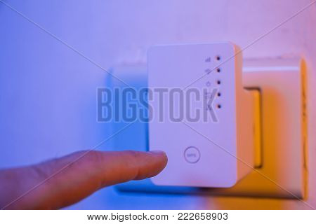 Man press with his finger on WPS button on WiFi repeater which is in electrical socket on the wall. The device help to extend wireless network in home or office.