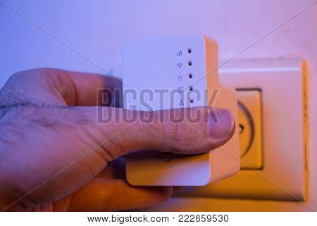 Man Press With His Finger On Wps Button On Wifi Repeater Which Is In Electrical Socket On The Wall