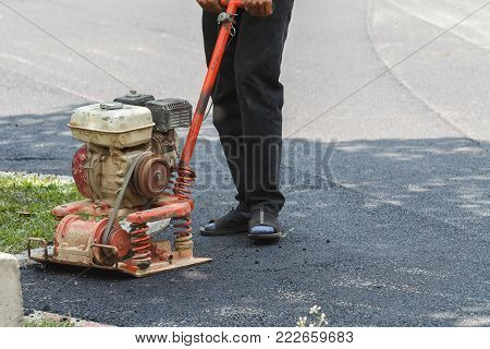 Worker Uses Vibratory Plate Compactor Compacting Asphalt At Road Repair