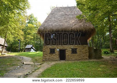 old Romanian house with straw roof and wooden and stone structure