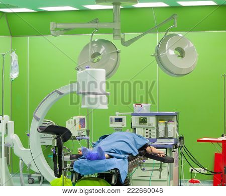 Surgery in modern hospital, patient lying prepared for operation.